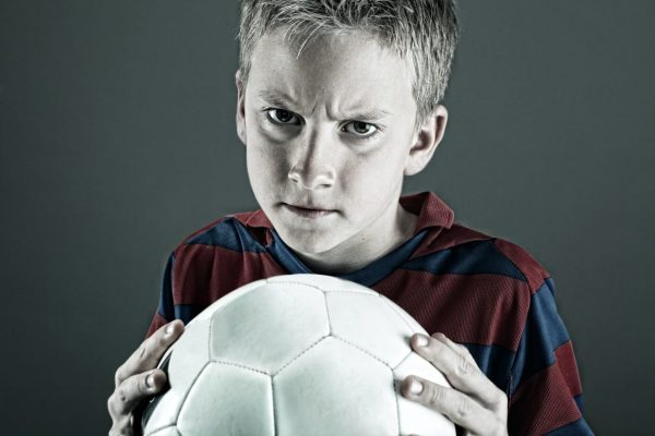 Angry child in red and blue shirt holding a ball